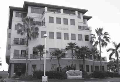 "Black and white photo of five-story building surrounded by palm trees with sign in front reading ""Ugland House."""