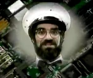 The face, hat and bow tie of the self-declared COMPUTER MAN appears in a circular cloud over a background image of a computer's circuit board.