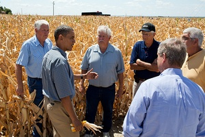 President Barack Obama speaking to a group of farmers in the midst of a corn field yellowed by drought