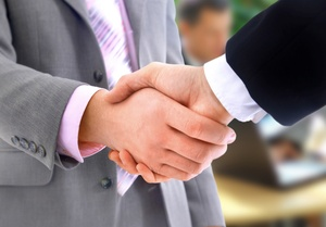 A close-up of a handshake by two men in business clothes.