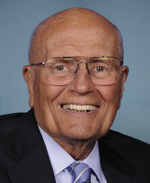 Official portrait of Rep. John Dingell, D-Mich., posing in suit in front of blue background