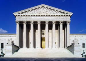 A view of the west facade of the U.S. Supreme Court building, full of grand columns set to a blue sky background.