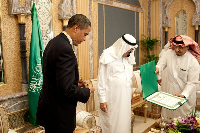 President Barack Obama in ornate room with Saudi flag and two men dressed in traditional Saudi garb