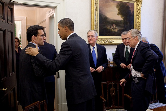 President Obama patting Eric Cantor on the back in a White House room as Sens. Mitch McConnell, Jon Kyl and Harry Reid look on.