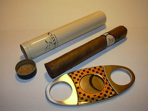 Picture of cigar, flanked by cigar tube and cigar cutter