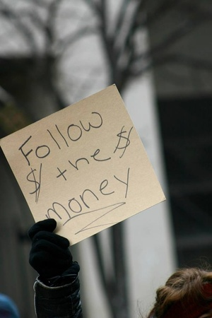 Someone at a demonstration holding up a sign that says follow the money.