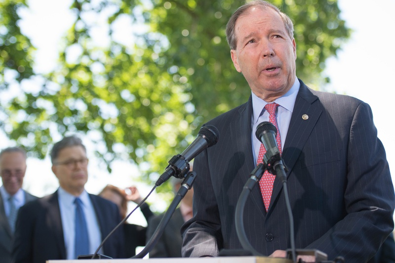 Sen. Tom Udall speaking at a podium outside.